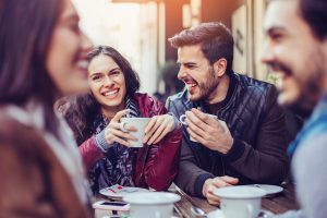 Happy young people having hot drinks outdoors in cafe
